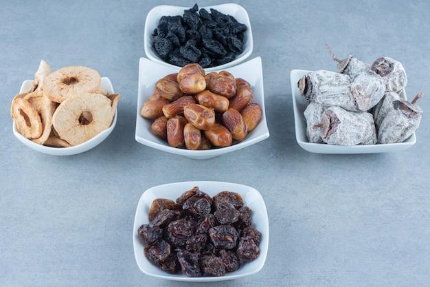 Een arrangement van verschillende smaken van turks fruit op een houten bord op marmeren tafel.