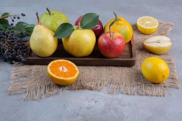 Een arrangement van verschillende soorten fruit op een houten bord en een doek op een marmeren achtergrond.