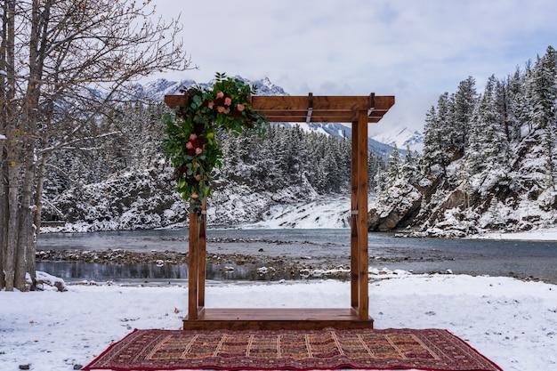 Een artistieke houten paviljoendecoratie en bow falls op de achtergrond in de winter