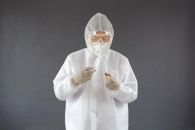 Een arts die een beschermend pak draagt met een spuit en absorbeert vaccinvloeistof uit een injectieflacon