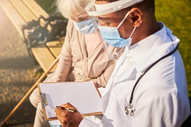 Een arts die gelaatsscherm en masker draagt en aantekeningen op een vel papier maakt