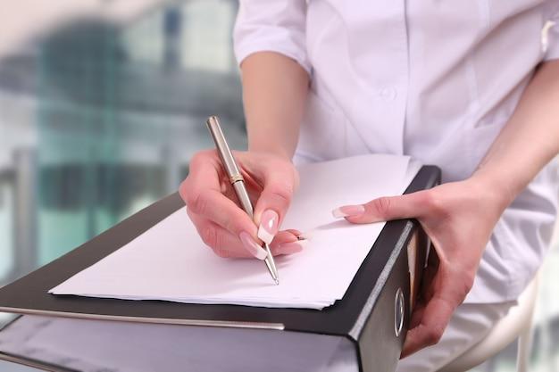 Een arts die in een klembord schrijft