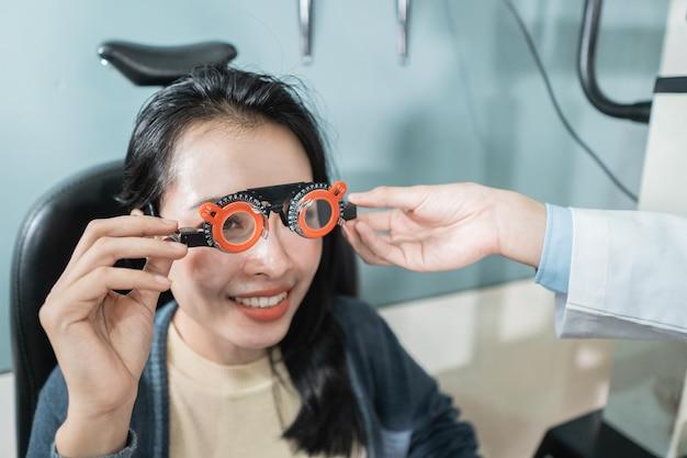 Een arts gebruikt een meetbril voor een vrouwelijke patiënt in een kamer in een oogkliniek