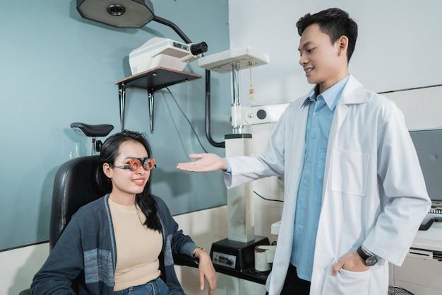 Een arts geeft aanwijzingen aan een vrouwelijke patiënt wanneer ze op het punt staat een controle te ondergaan in een oogkliniek