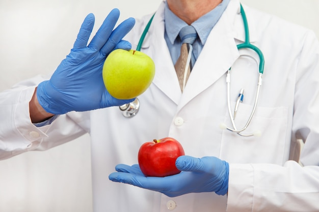 Een arts in beschermende handschoenen toont een appel