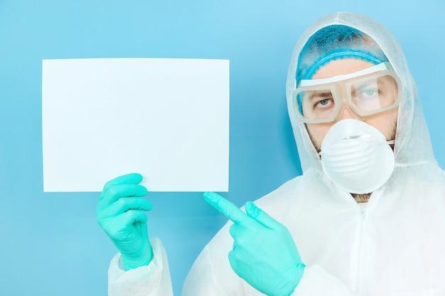 Een arts in een beschermend pak, een masker en handschoenen houdt een vel papier vast. de dokter vecht tegen het coronavirus. stop de verspreiding van het covid 19-virus.