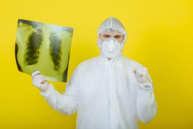 Een arts in een beschermend pak met een röntgenfoto van de longen toont een goedkeurend bord met zijn hand op een gele achtergrond in de studio. het concept van het coronovirus covid-19.