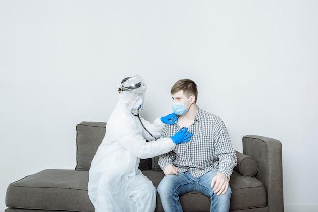 Een arts in een beschermend pak pbm-hazmat in een masker en handschoenen onderzoekt de patiënt en luistert met een stethoscoop naar ademhaling