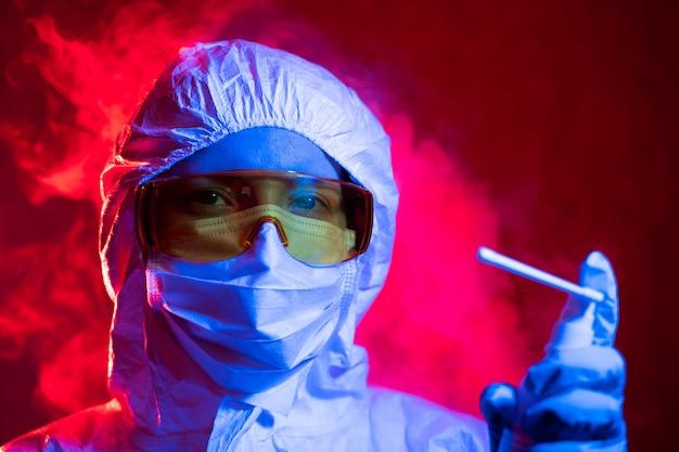 Een arts in een beschermend pak spuit een desinfecterende spray. coronavirus pandemisch quarantaineconcept ncov-2019