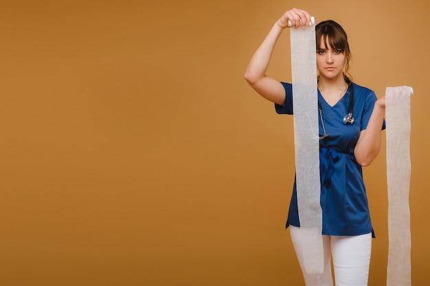 Een arts in een blauwe kamerjas houdt een gedraaid gaasverband vast om wonden op een bruine achtergrond aan te brengen