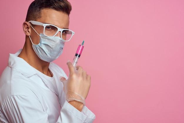 Een arts in een medisch masker en handschoenen houdt een spuit in de handen van een injectielaboratorium.