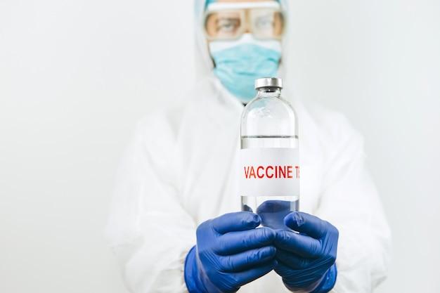 Een arts in een witte jas en blauwe handschoenen heeft een reageerbuis met spuit met een coronavirusvaccin. covid 2019-vaccininjectie. pandemisch coronavirus uit 2020. vaccin test.