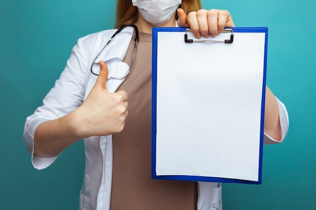 Een arts in het gezichtsmasker van de medische toga dat op blauw wordt geïsoleerd. houd het klembord vast met een lege, lege werkruimte.