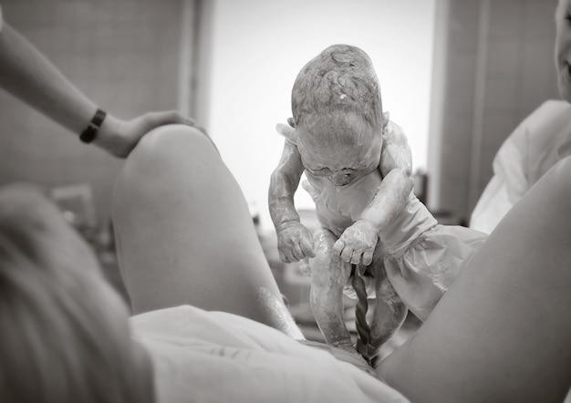Een arts in het ziekenhuis met een pasgeboren baby, zwart-wit foto, de arts toont de pasgeborene aan de moeder.