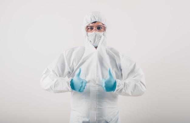 Een arts in medische handschoenen en beschermend kostuum die duimen op lichte achtergrond tonen. coronavirus