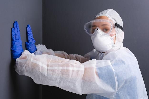 Een arts in uniform die zijn handen tegen een grijze muur drukt, kijkt naar de camera