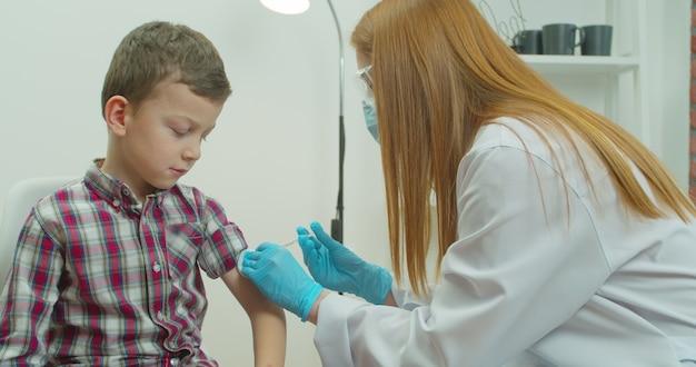 Een arts injecteert een vaccin in de schouder van de jongen.