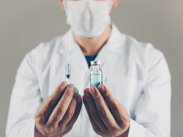 Een arts met het flesje van de maskerholding en spuit in zijn handen zijaanzicht