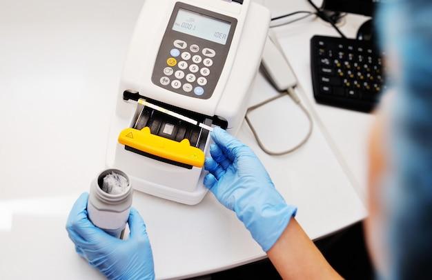 Een arts of laboratoriumassistent maakt een urinetest op een urineanalysator