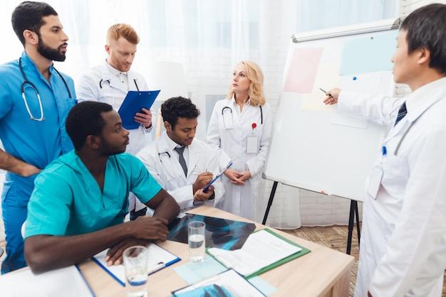 Een arts toont papier van andere artsen op een wit bord.