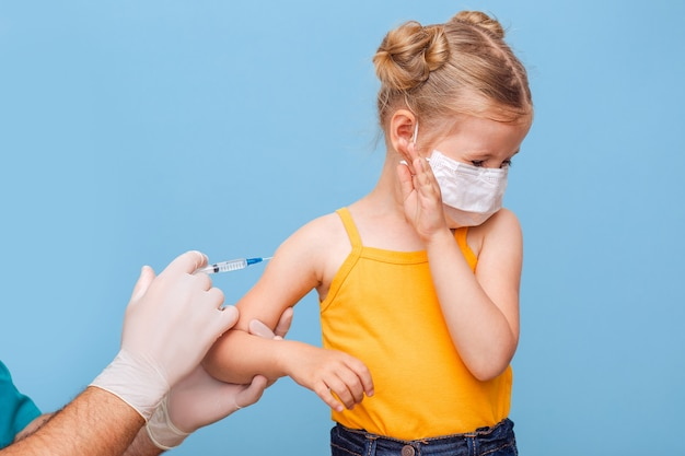 Een arts vaccineert een klein blond meisje met een medisch masker
