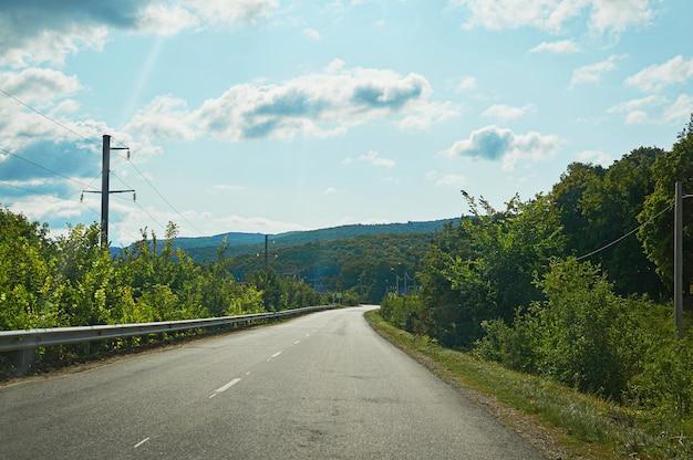 Een asfaltweg in het bos en de bergen.