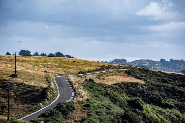 Een asfaltweg met weideheuvels op een bewolkte dag in chilo