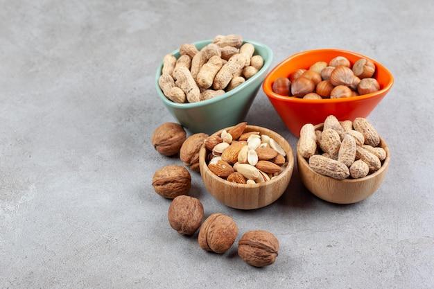 Een assortiment van verschillende soorten noten in houten kommen op marmeren achtergrond. hoge kwaliteit foto