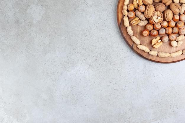 Een assortiment van verschillende soorten noten op een houten bord op marmeren achtergrond.