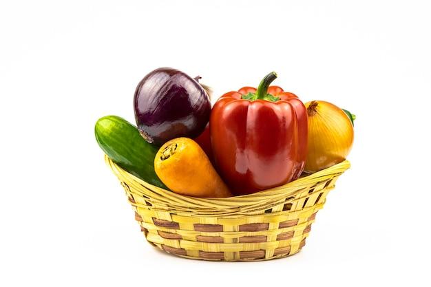 Een assortiment van verse groenten in een rieten mand geïsoleerd op een witte achtergrond.