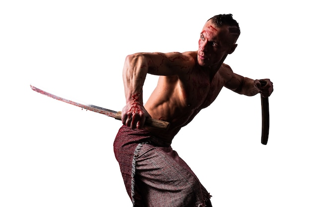Een atletische man in bloed met een japans zwaard toont vechttechnieken geïsoleerd