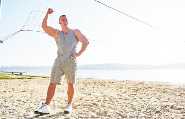 Een atletische man kijkt naar zee op wild zandstrand.