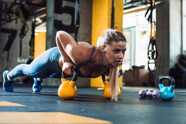 Een atletische vrouw die opdrukoefeningen op ketelkogel doet