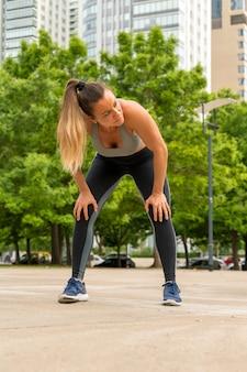 Een atletische vrouw die zich met haar handen op haar knieën bevindt