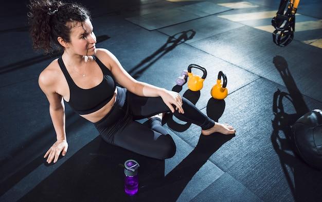 Een atletische vrouwenzitting dichtbij oefeningsmateriaal in gymnastiek
