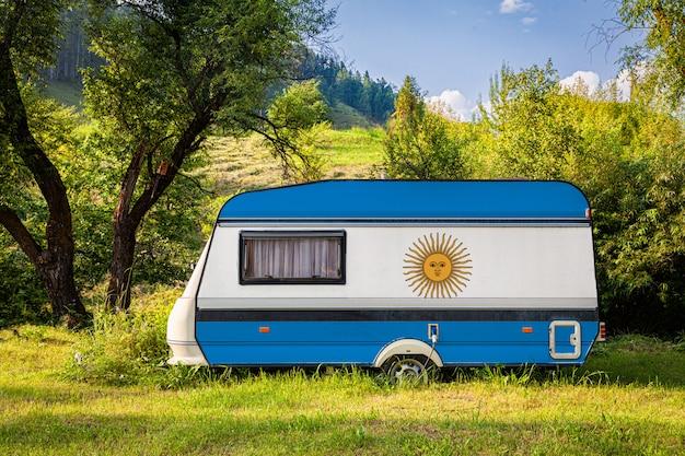 Een auto-aanhangwagen, een camper, geschilderd in de nationale vlag van argentinië, staat geparkeerd in een bergachtig gebied.