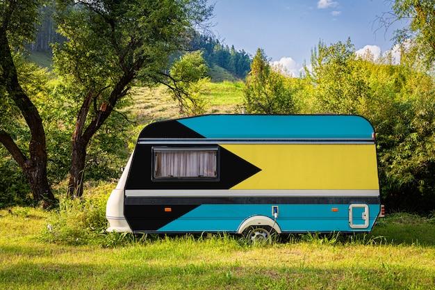 Een auto-aanhangwagen, een camper, geschilderd in de nationale vlag van bahama's staat geparkeerd in een bergachtige.