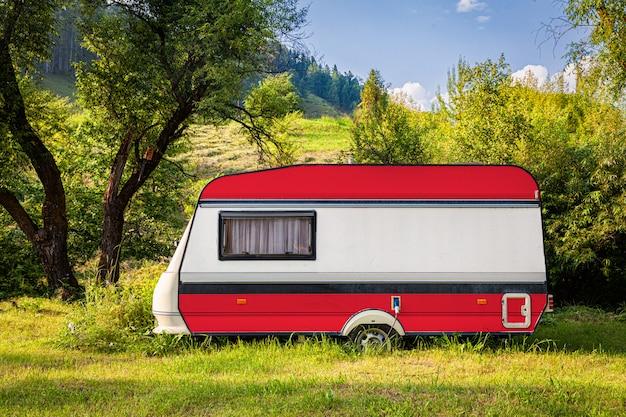Een auto-aanhangwagen, een camper, geschilderd in de nationale vlag van oostenrijk, staat geparkeerd in een bergachtige.