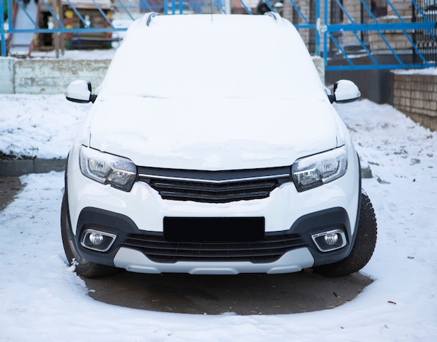 Een auto die op straat geparkeerd staat, is bedekt met verse witte sneeuw
