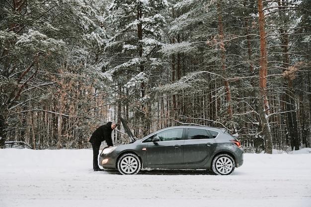 Een auto met een open kap op de achtergrond van een winterbos