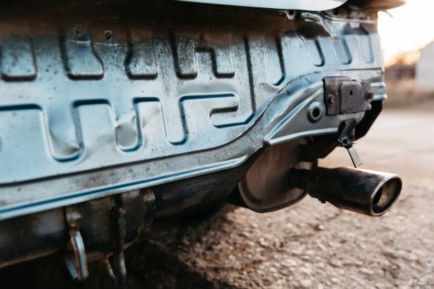 Een auto zonder bumper, de uitlaatpijp is zichtbaar. reparatie is nodig. autoverzekering concept