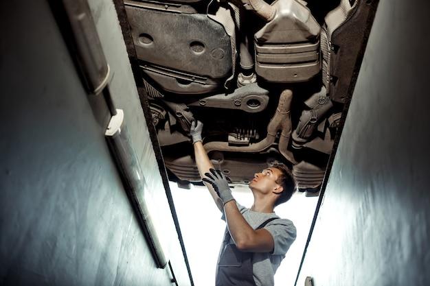 Een automonteur controleert een opgetilde auto. auto onderhoud.