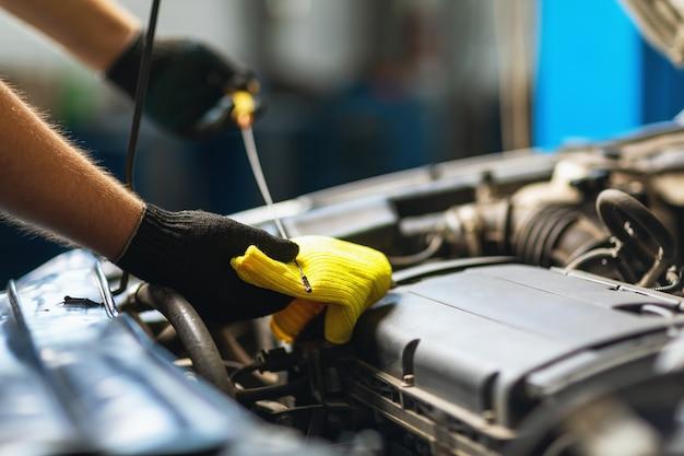 Een automonteur controleert het oliepeil in een automotor met een speciale peilstok