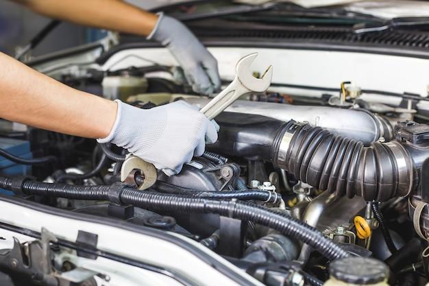 Een automonteur doet een autoreparatie in een reparatiewerkplaats.