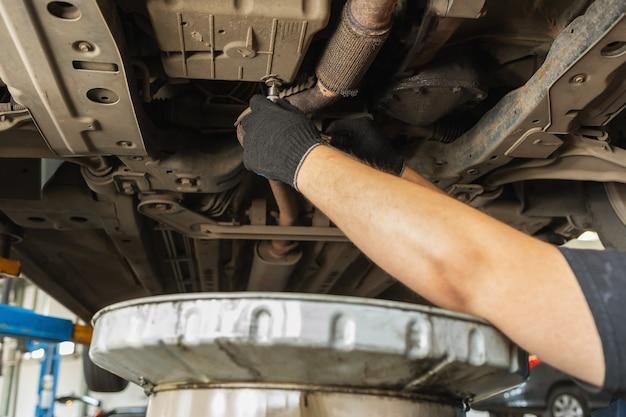 Een automonteur draait de olieaftapplug in het carter van een auto vast met een sleutel