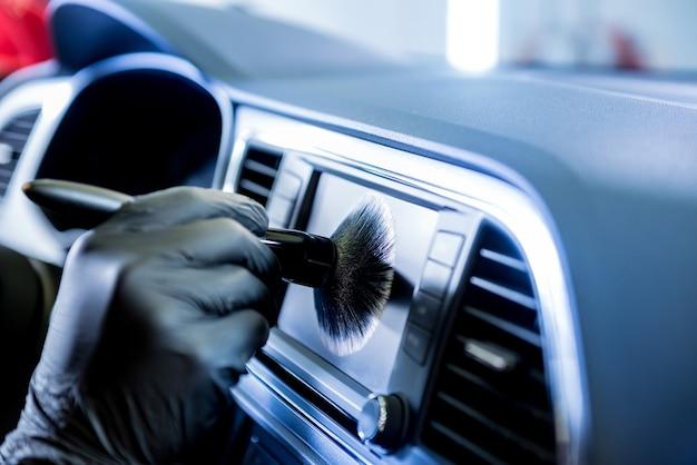 Een autoservicemedewerker maakt de autoconsole schoon met een speciale borstel