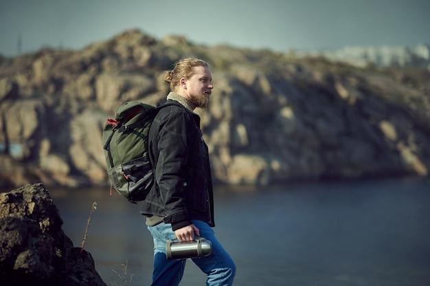 Een avonturier die bovenop een klif staat en de schoonheid van de natuur bewondert.