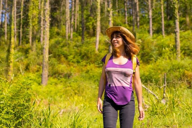 Een avontuurlijke wandelaar die lacht naast een paar dennenbomen in het bos
