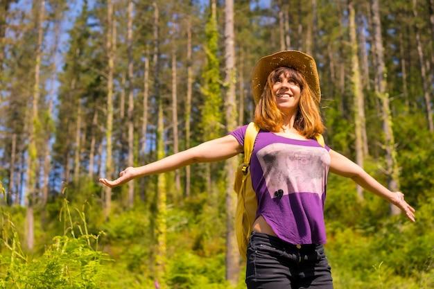 Een avontuurlijke wandelaar heel blij naast een paar dennenbomen in het bos