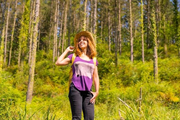 Een avontuurlijke wandelaar heel blij naast enkele pijnbomen